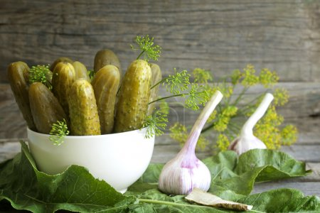 Pickles gherkins salted cucumbers still life on old planks