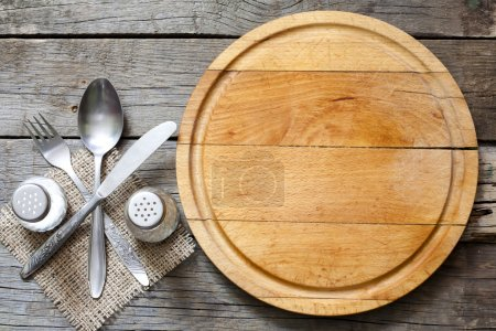 Cutlery and vintage empty cutting board food background concept