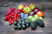 Summer wild berry fruits on vintage board still life concept