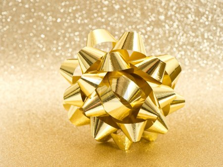beautiful golden bow on shiny background