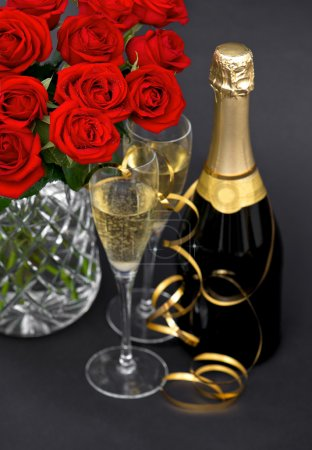 Red roses and champagne. festive decoration