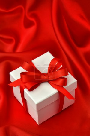 White gift box with red ribbon over silk