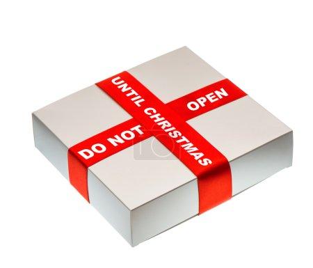 Foto de Closeup gris de caja de regalo con cinta de raso roja y el texto no abrir hasta Navidad. aislado sobre fondo blanco - Imagen libre de derechos