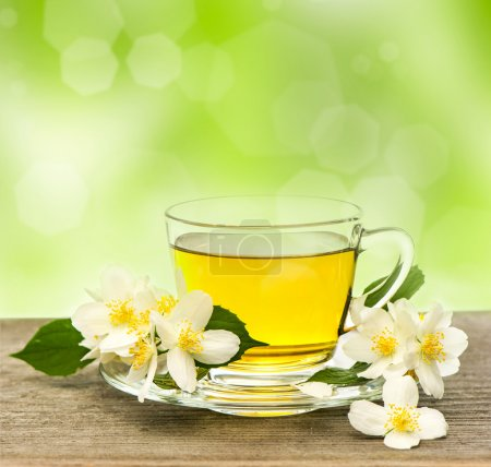 Photo for Cup of tea with jasmine flowers on wooden table over blurred green background - Royalty Free Image