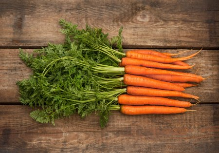 Bunch of fresh carrots over wooden background
