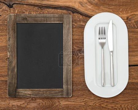 Photo pour Tableau noir pour menu sur table en bois avec plaque blanche, couteau et fourchette - image libre de droit
