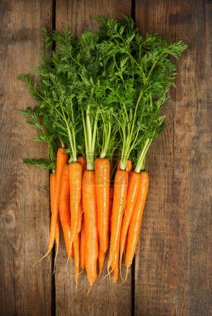 fresh carrots with green leaves over wooden
