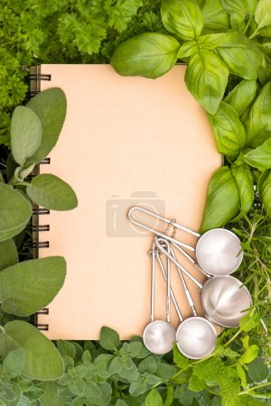 Recipe book with variety fresh herbs