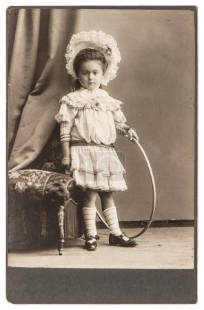 Old photo of little girl with toy wearing vintage dress