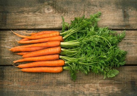 Photo for Roots of fresh carrots with green leaves over wooden background. - Royalty Free Image