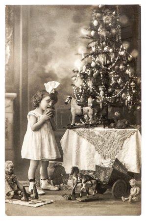 Photo pour Photo antique de littele girl avec arbre de Noël et jouets vintage. Ancienne carte postale vers 1900, Allemagne - image libre de droit