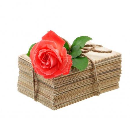 Photo pour Empilement de vieilles lettres d'amour et cartes postales avec fleur de rose rouge isolée sur fond blanc. Image sentimentale nostalgique - image libre de droit
