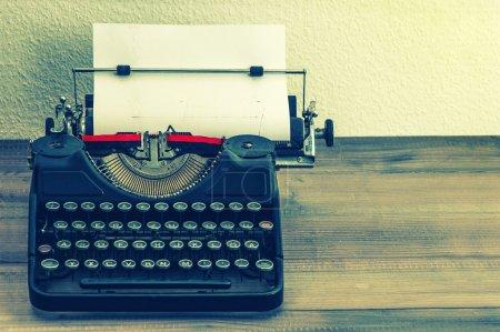 Photo pour Machine à écrire rétro avec page en papier blanc sur table en bois. style vintage image tonique - image libre de droit