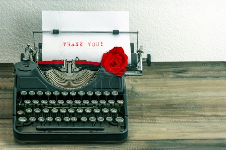 Photo for Vintage typewriter with white paper page and red rose flower. sample text Thank You! - Royalty Free Image