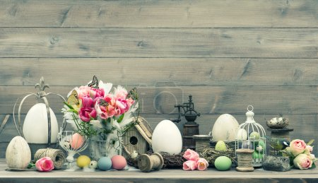 Photo for Easter home interior decoration with pink tulip flowers and colored eggs. Shabby chic. Vintage style toned picture - Royalty Free Image