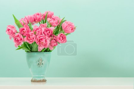 pastel pink tulip flowers over turquoise