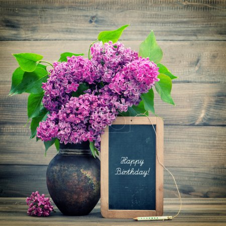 bouquet of lilac flowers. blackboard with text Happy Birthday!