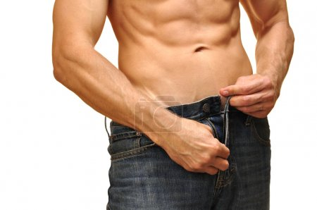 Photo for Sexy man with lean abdominals unzips his jeans on white background - Royalty Free Image