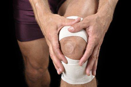 Foto de Primer plano del hombre Atlético tendiendo la rodilla lesionada envuelta en fondo negro - Imagen libre de derechos
