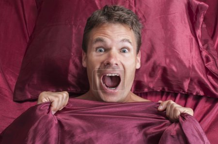 Photo for Closeup of terrified Caucasian man reacting to nightmare and screaming under red bed sheets - Royalty Free Image