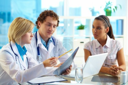 Photo for Pretty patient listening to therapeutists at medical consultation - Royalty Free Image