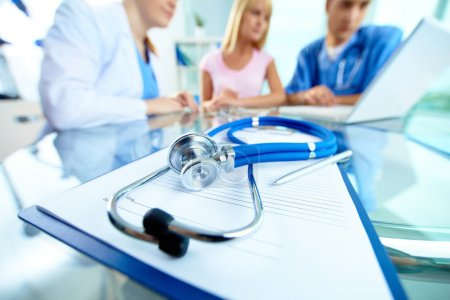 Photo for Close-up of stethoscope and paper on background of doctors and patient working with laptop - Royalty Free Image