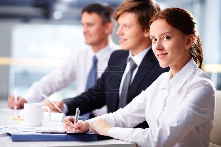 Photo pour Trois entreprises assises au séminaire avec une femme souriante au premier plan - image libre de droit