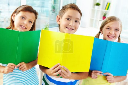 Photo for Portrait of happy classmates with books smiling at camera in classroom - Royalty Free Image