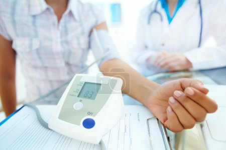 Photo pour Gros plan du tonomètre par le bras du patient lors de la mesure de la pression artérielle lors d'une consultation médicale - image libre de droit