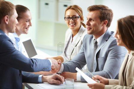 Photo pour Image d'hommes d'affaires confiants serrant la main à la réunion - image libre de droit