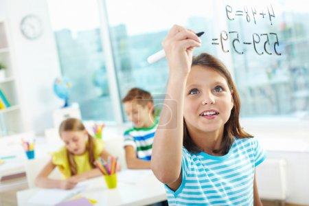 Photo pour Portrait de jolie fille faisant des sommes à bord transparent avec deux camarades de classe sur fond - image libre de droit