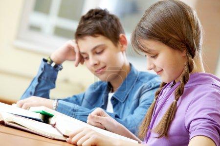 Photo pour Portrait de livre de lecture adolescente avec son camarade de classe à l'arrière-plan - image libre de droit