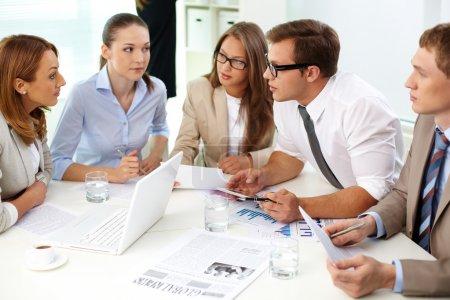 Photo pour Image de partenaires confiants regardant leur collègue à la réunion - image libre de droit