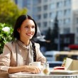 Image of happy female in open air cafe having coff...