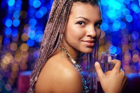 Foto de Retrato de una hermosa mujer étnica con champán mirando a la cámara - Imagen libre de derechos