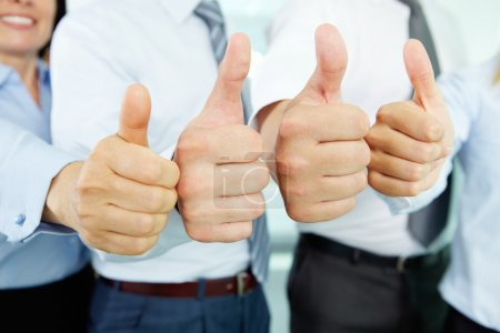Photo for Close-up of business team holding their thumbs up - Royalty Free Image