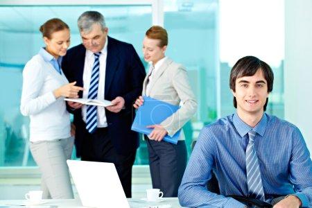 Foto de Retrato de seguro líder mirando a cámara con empleados trabajando detrás de - Imagen libre de derechos