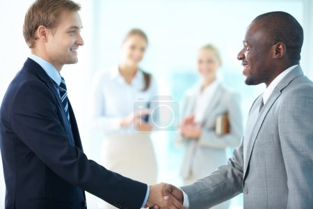 Photo for Portrait of happy leaders handshaking and two females applauding on background - Royalty Free Image