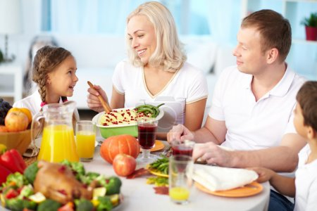 Photo for Portrait of happy couple and their children sitting at festive table and going to eat mashed potatoes - Royalty Free Image