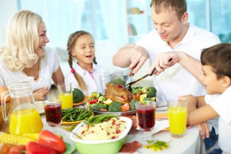 Photo for Portrait of happy couple and their children sitting at festive table and going to eat roasted turkey - Royalty Free Image