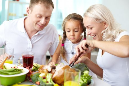 Photo for Portrait of happy couple and their daughter sitting at festive table and going to eat roasted turkey - Royalty Free Image