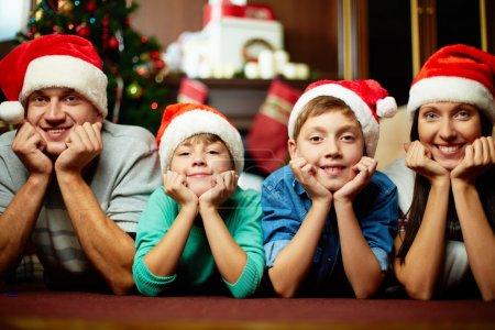 Photo pour Portrait de famille en majuscules santa caméra en regardant le soir de Noël - image libre de droit