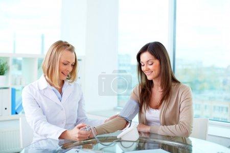 Photo pour Portrait d'un praticien confiant mesurant la pression artérielle du patient - image libre de droit