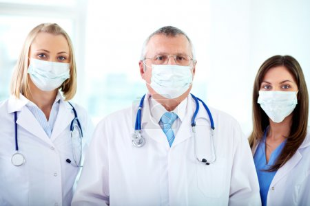 Photo for Portrait of three therapeutists in masks looking at camera - Royalty Free Image
