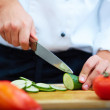 Image of male hand with knife cutting cucumbers on...