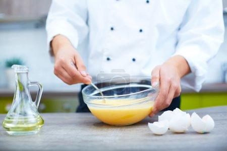 Photo pour Image des mains de cuisinier mélangeant les œufs crus dans un bol - image libre de droit