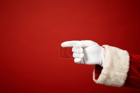 Photo for Photo of Santa Claus gloved hand in pointing gesture - Royalty Free Image
