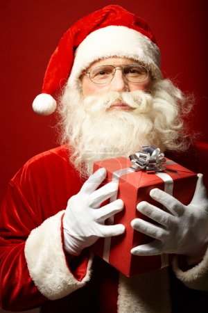 Photo for Photo of Santa Claus with red giftbox looking at camera - Royalty Free Image
