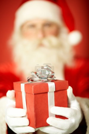 Photo for Photo of Santa Claus giving xmas present with focus on his hands - Royalty Free Image