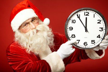 Photo for Photo of Santa pointing at clock showing five minutes to midnight - Royalty Free Image